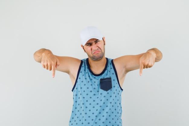 Junger mann, der in blauem unterhemd, mütze unten zeigt und unzufrieden aussieht. vorderansicht.