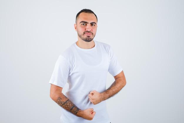 Junger mann, der in boxerpose im weißen t-shirt steht und glücklich aussieht looking