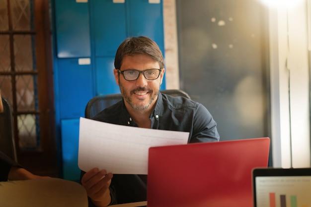 Junger mann, der in den modernen büroräumen arbeitet