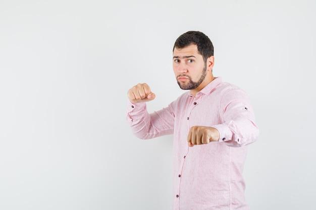 Junger mann, der in der boxerhaltung im rosa hemd steht und stark schaut