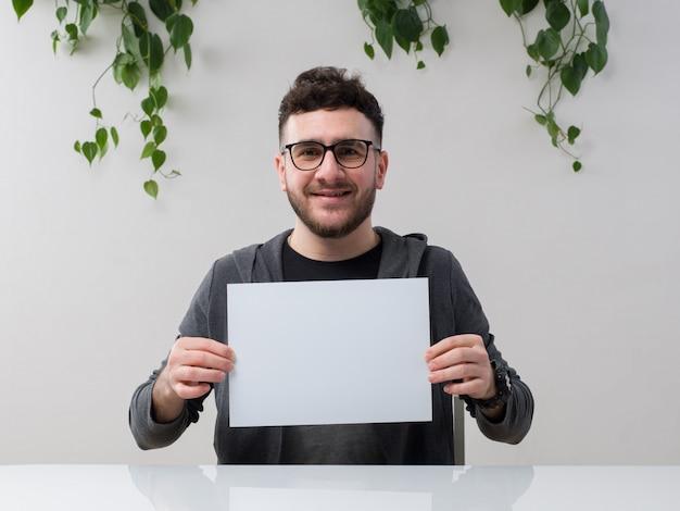 Junger mann, der in der brille sitzt, beobachtet graue jacke lächelnd, die leeres papier zusammen mit pflanze auf weiß hält