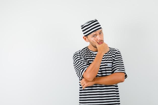 Junger mann, der in der denkenden haltung im gestreiften t-shirt, im hut steht und vernünftig aussieht.