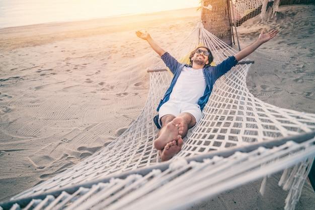 Junger mann, der in der hängematte am strand entspannt. glück, urlaubsfreiheit und reisekonzept. offene arme