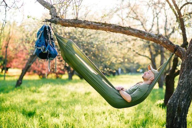 Junger mann, der in der hängematte im sonnigen sommerpark entspannt