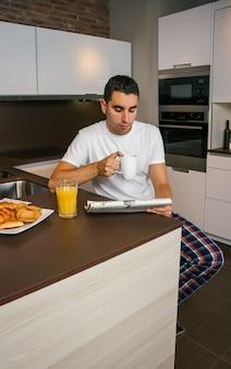 Junger mann, der in der küche frühstückt und die zeitung liest