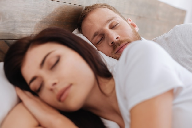 Junger mann, der in der nähe seiner frau schläft und einen traum von ihrem langen glücklichen zusammenleben sieht