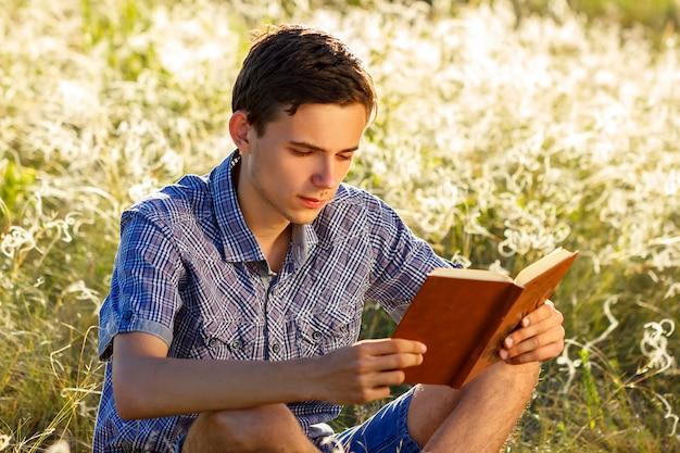 Junger mann, der in der natur sitzt, ein buch lesend