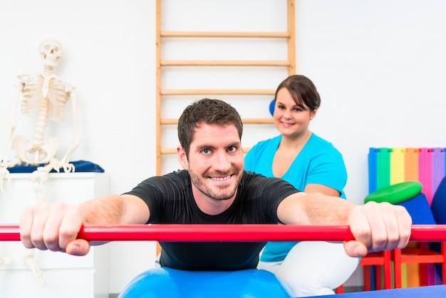 Junger mann, der in der physiotherapie auf schweizer ball mit gymnastischem stock ausarbeitet
