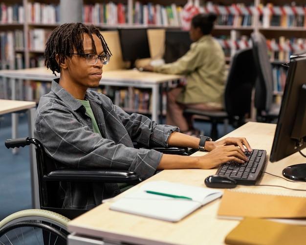 Junger mann, der in der universitätsbibliothek studiert