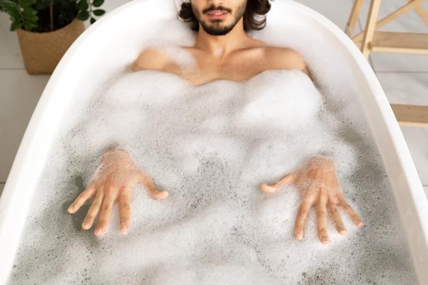 Junger mann, der in der weißen badewanne liegt, die mit heißem wasser gefüllt wird und schaum durch seine hände berührt, während er sich entspannt