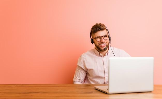Junger mann, der in einem call-center blinzelt, lustig, freundlich und sorglos arbeitet