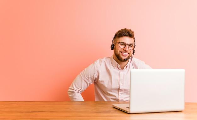 Junger mann, der in einem call-center überzeugt arbeitet, hände auf ihm hüften halten.