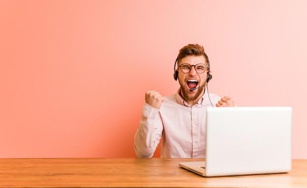 Junger mann, der in einem call-center-zujubeln sorglos und aufgeregt arbeitet. sieg-konzept.