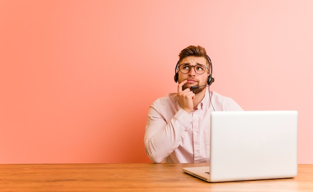 Junger mann, der in einem callcenter arbeitet, das mit zweifelhaftem und skeptischem ausdruck seitwärts schaut.