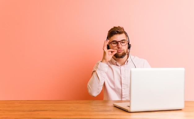 Junger mann, der in einem callcenter mit den fingern auf den lippen arbeitet, die ein geheimnis halten