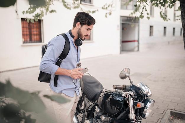Junger mann, der in einem motorradspiegel schaut