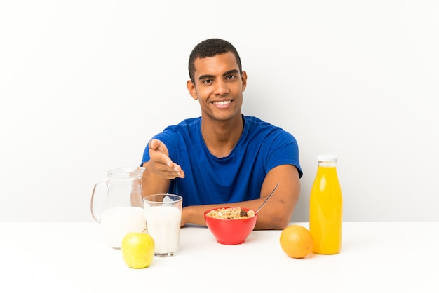 Junger mann, der in einem tabellenhändeschütteln frühstückt