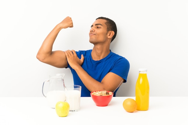 Junger mann, der in einer tabelle bildet starke geste frühstückt