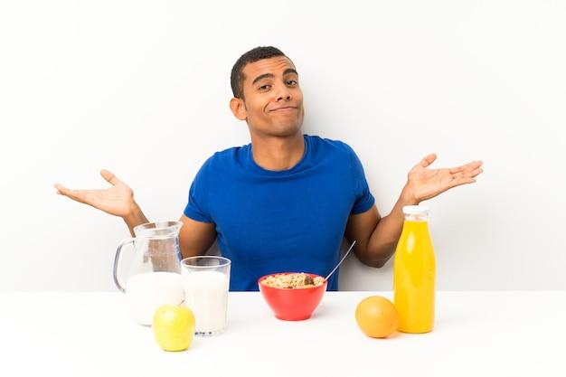 Junger mann, der in einer tabelle hat zweifel mit verwirren gesichtsausdruck frühstückt