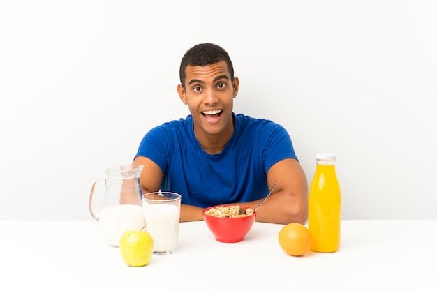 Junger mann, der in einer tabelle mit überraschungsgesichtsausdruck frühstückt