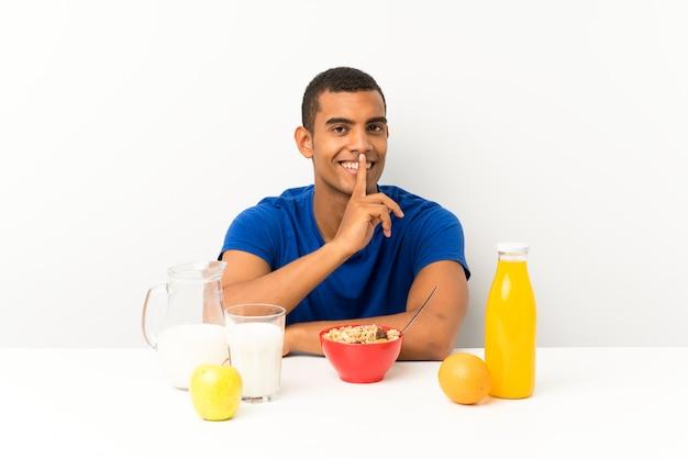 Junger mann, der in einer tabelle tut ruhegeste frühstückt