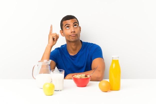 Junger mann, der in einer tabelle zeigt mit dem zeigefinger eine großartige idee frühstückt