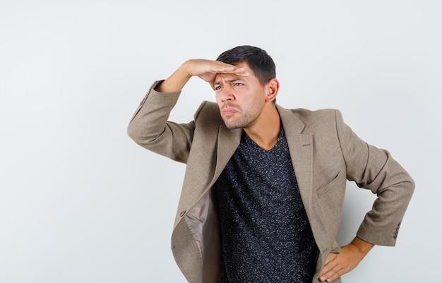 Junger mann, der in graubrauner jacke, schwarzem hemd wegschaut und interessiert aussieht. vorderansicht.