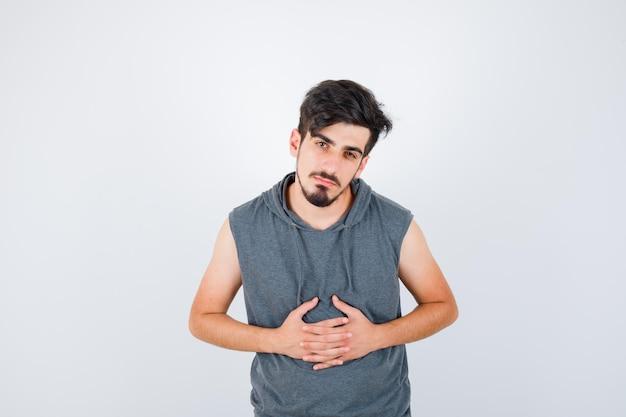 Junger mann, der in grauem t-shirt die hände auf dem bauch hält und ernst aussieht