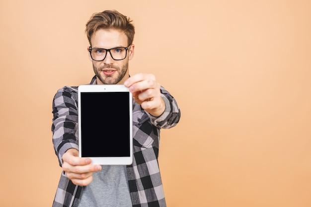 Junger mann, der in händen tablet-computer mit leerem bildschirm hält