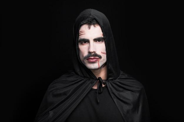 Junger mann, der in halloween-kostüm aufwirft