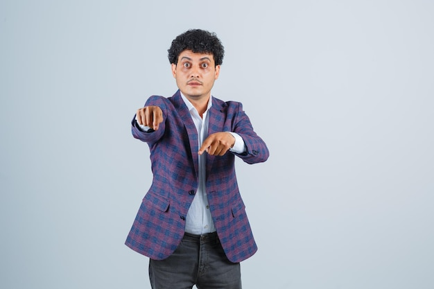 Junger mann, der in hemd, jacke, hose nach unten zeigt und ängstlich aussieht, vorderansicht.