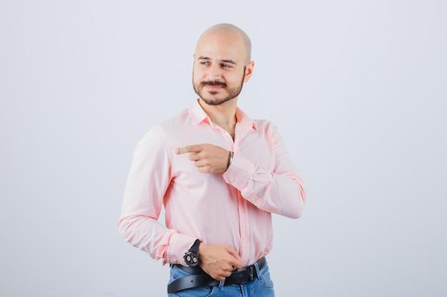 Junger mann, der in hemd, jeans auf die linke seite zeigt und glücklich aussieht. vorderansicht.