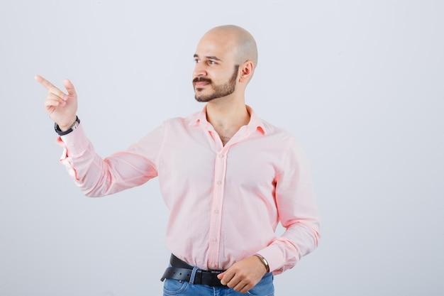 Junger mann, der in hemd, jeans beiseite zeigt und glücklich aussieht, vorderansicht.