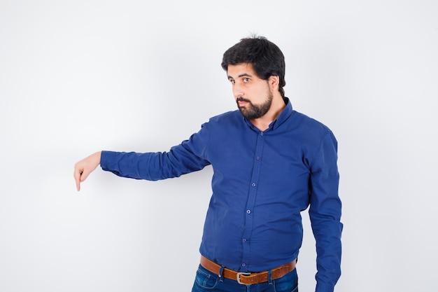 Junger mann, der in hemd, jeans nach unten zeigt und selbstbewusst aussieht. vorderansicht.