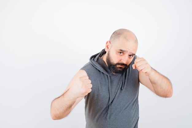 Junger mann, der in kampfpose in ärmellosem hoodie steht und selbstbewusst aussieht. vorderansicht.