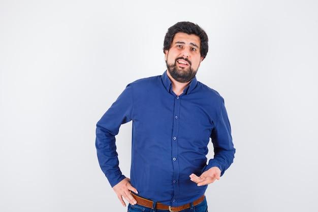 Junger mann, der in königsblauem hemd spricht und gesprächig aussieht, vorderansicht.
