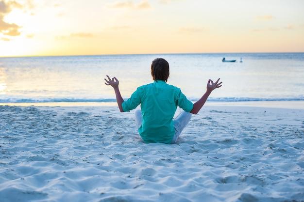 Junger mann, der in lotussitz auf weißem sandstrand sitzt