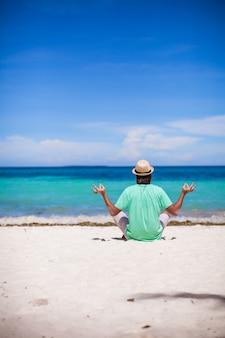 Junger mann, der in lotussitz auf weißem tropischem strand sitzt