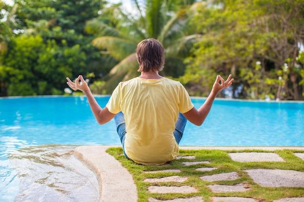 Junger mann, der in lotussitz nahe dem pool sitzt
