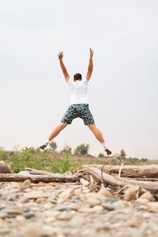Junger mann, der in natur springt