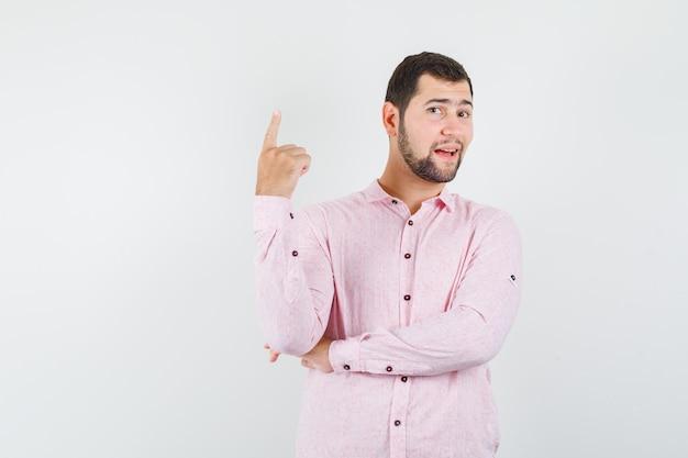 Junger mann, der in rosa hemd zeigt und fröhlich schaut