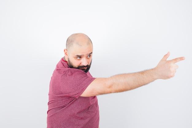 Junger mann, der in rosa t-shirt nach vorne zeigt, vorderansicht.