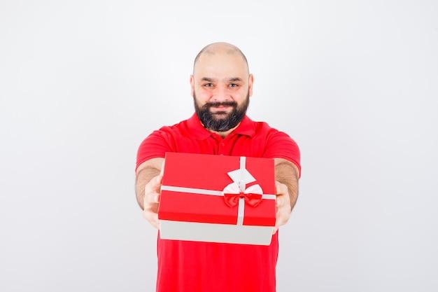 Junger mann, der in rotem hemd ein geschenk gibt und geliebt aussieht, vorderansicht.