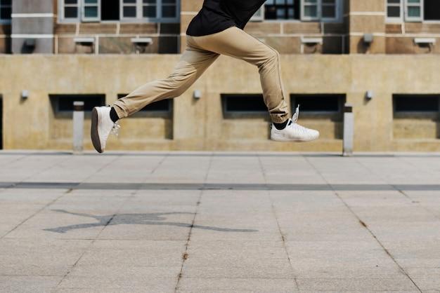 Junger mann, der in scount des universitätsgeländegebäudes springt