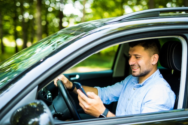 Junger mann, der in seinem auto mit handy fährt