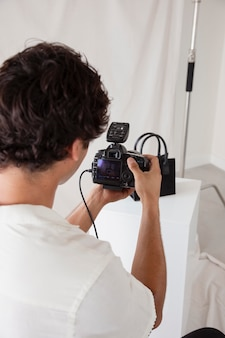 Junger mann, der in seinem fotostudio arbeitet