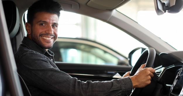 Junger mann, der in seinem neuwagen in einem ausstellungsraum lächelt