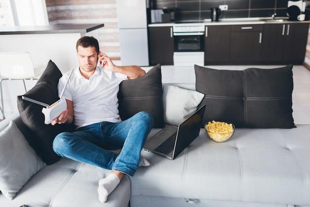 Junger mann, der in seiner eigenen wohnung fernsieht. kerl sitzt auf der couch und telefoniert.