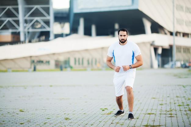 Junger mann, der in städtische umwelt läuft