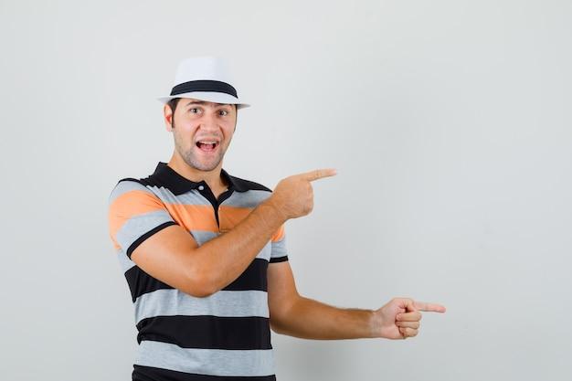 Junger mann, der in t-shirt, hut beiseite zeigt und fröhlichen raum für text sucht